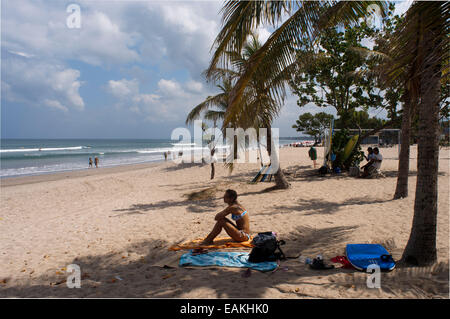 Indonesien, Bali, Kuta, Strand, Frau Sonnenbaden.  Sonnenbad am Strand von Kuta. Surfunterricht. Bali. Kuta ist - Stockfoto