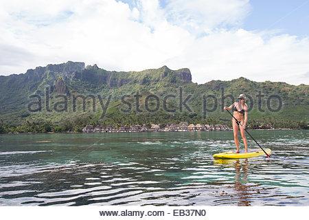 Eine Frau Stand-up Paddle boarding, Insel Moorea, Französisch-Polynesien. - Stockfoto