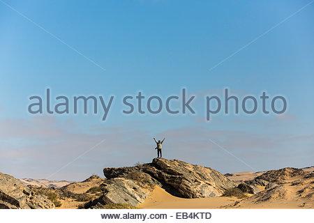 Eine Person steht auf einem Felsvorsprung inmitten der Dünen und Felsen auf Namibias Skelettküste. - Stockfoto