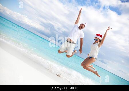 Glückliches Paar feiert Weihnachten am Strand, in die Luft springen - Stockfoto