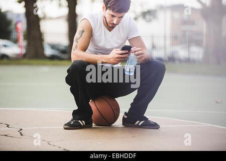 Junge männliche Basketball sitzend auf Kugel SMS auf smartphone - Stockfoto