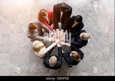 Draufsicht der Unternehmerinnen und Unternehmer im Kreis mit Hände zusammen - Stockfoto