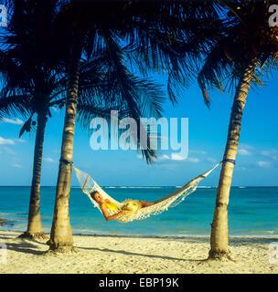 Junge Frau in Hängematte zwischen Palmen am karibischen Strand Guadeloupe zu schlafen - Stockfoto