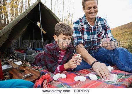 Vater und Sohn Spielkarten vor Zelt - Stockfoto