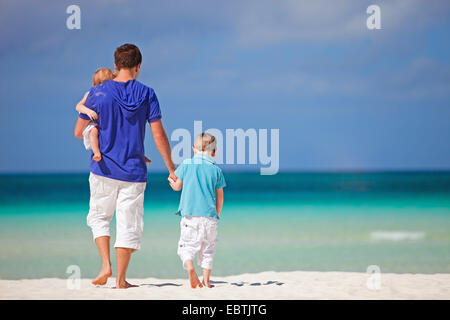 Vater mit seinen Kindern am tropischen Strand zu Fuß - Stockfoto