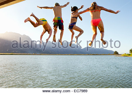 Familie, in Bademode, springen in einen See von einem Steg - Stockfoto