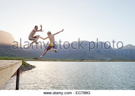 Vater und Sohn von der Anlegestelle in See springen - Stockfoto