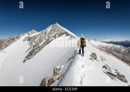 Bergsteiger auf dem Gipfelgrat während der Besteigung des Mt Hoher Weißzint, Gipfelkreuz an der Rückseite, wichtigsten - Stockfoto