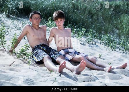 Zwei jungen am Strand sitzen - Stockfoto