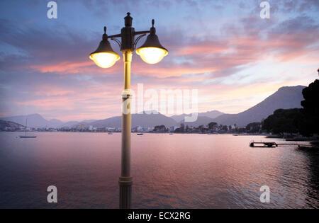 Blick auf die beleuchtete Straßenleuchte mit Bucht und die Berge im Hintergrund - Stockfoto