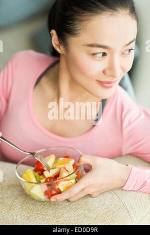 Glückliche junge Frau Obstsalat Essen - Stockfoto