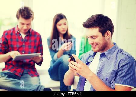Student auf der Suche in Smartphone in der Schule - Stockfoto