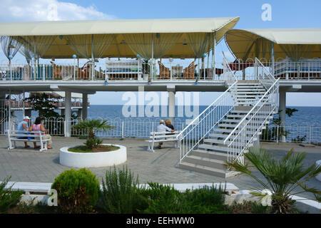 Paare, die auf den Bänken sitzen in der Nähe von Seaside Restaurant im Resort Stadt von Aluschta, Krim, Russland - Stockfoto