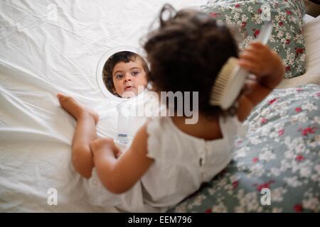 Mädchen (2-3) Kämmen Haare auf dem Bett mit Spiegel - Stockfoto