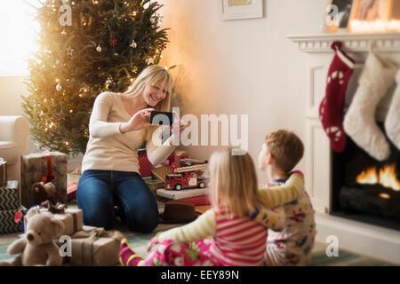 Mutter mit Kinder (4-5, 6 und 7) Eröffnung Weihnachtsgeschenke und fotografieren - Stockfoto
