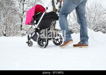 Ein Vater mit seinem Baby im Buggy auf einer verschneiten Strecke - Stockfoto