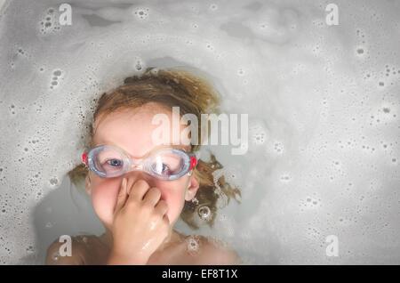 Junge (6-7) mit Brille spielen in Badewanne - Stockfoto