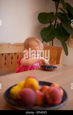 Junges Kind essen Obst an einem Esstisch - Stockfoto