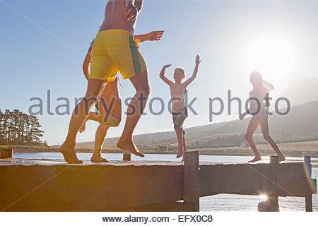 Glückliche Familie laufen und springen auf Steg - Stockfoto