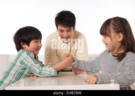 Jungen und Mädchen in einem Armdrücken Vater tun Schiedsrichter - Stockfoto