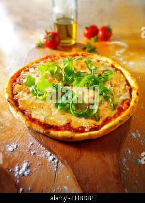 Ganze Käse & Tomate traditionelle Pizza Margherita mit Rucola garniert - Stockfoto