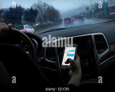 In dem Auto texting Fahrerin in l/h Fahrzeug fahren heimlich SMS-Smartphones während der Fahrt auf langen nassen - Stockfoto