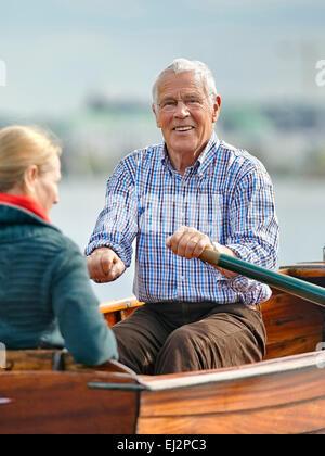 Senior und seine Tochter reiten auf einem Ruderboot - Stockfoto