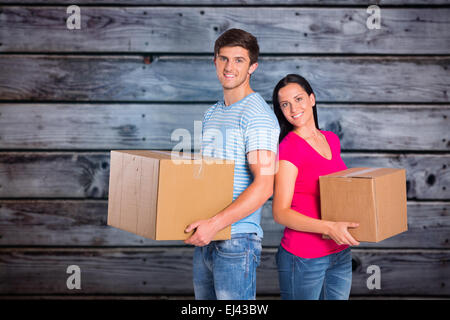 Zusammengesetztes Bild jungen Paares halten Umzugskartons - Stockfoto