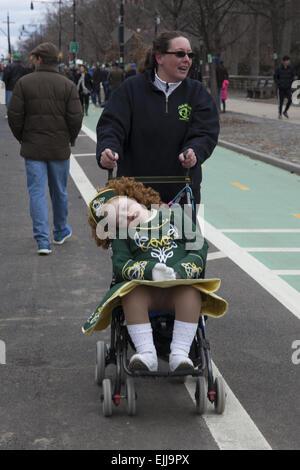 Mutter schiebt müde Tochter im Kinderwagen nach dem Tanzen an der irischen Parade in Park Slope, Brooklyn, NY. - Stockfoto