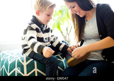 Mutter hilft Sohn (6-7) putting Schuh auf - Stockfoto