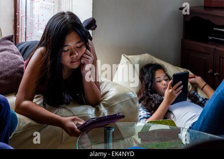 Zwei Mädchen spielen auf Ihren Ipads/Tabletten, Sussex, UK - Stockfoto