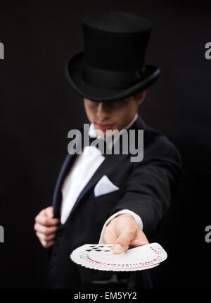 Zauberer in Hattrick zeigt mit Spielkarten - Stockfoto