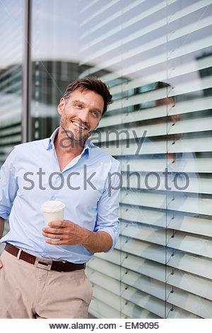 Porträt von reifer Geschäftsmann gelehnt Bürofenster Kaffeetrinken - Stockfoto