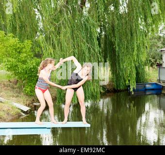 Zwei Schwestern spielen kämpfen auf Sprungbrett über See - Stockfoto