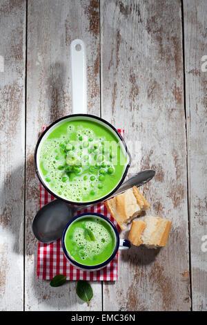 Topf und Tasse Erbsensuppe, Löffel, in Scheiben geschnittene Baguette und Tuch auf Holz - Stockfoto
