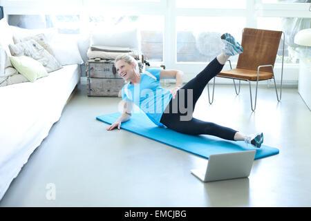 Frau mit Laptop Ausübung auf Gymnastikmatte im Wohnzimmer - Stockfoto