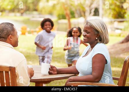 Großeltern entspannen, während ihre Enkel im Garten spielen - Stockfoto