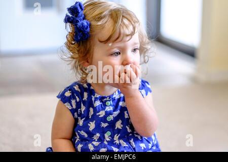 Ein 14 Monate altes Baby isst einen Cracker auf dem Boden sitzend. - Stockfoto