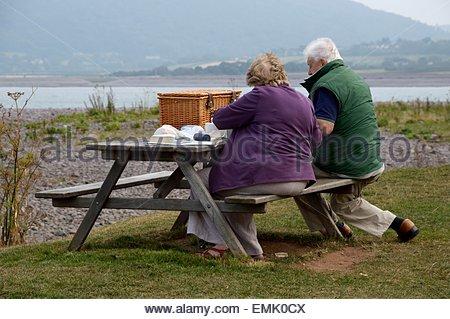 Älteres Paar, sitzen an einem Tisch und Bank, mit einem Picknick am Meer an einem bewölkten Tag - Stockfoto