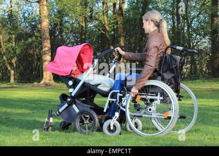 Eine Mutter im Rollstuhl schob einen Kinderwagen mit baby - Stockfoto