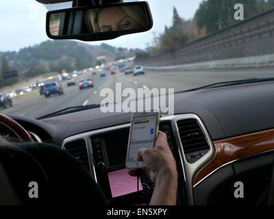 TEXTING FAHREN USA weibliche Fahrer in l/h Fahrzeug fahren sms mit dem iPhone Smartphone während der Fahrt auf der - Stockfoto
