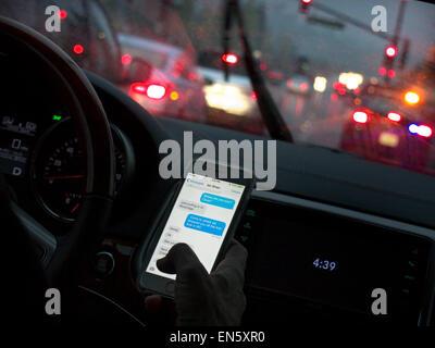 In dem Auto Fahrerin in l/h Fahrzeug fahren heimlich SMS mit Smartphone während der Fahrt bei Besetzt nasse Regen - Stockfoto