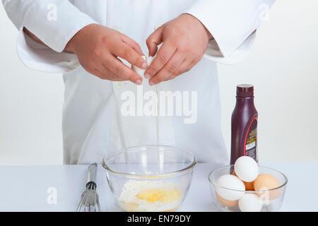 Küchenchef knacken Ei in Schüssel - Stockfoto