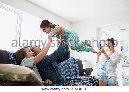 Mutter fotografieren spielerisch Vater Hebe Tochter overhead - Stockfoto
