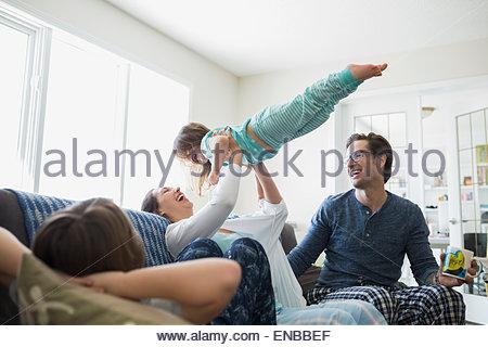 Spielerische Mutter Tochter overhead auf Sofa heben - Stockfoto