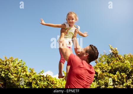 Kleines Mädchen, die vorgibt, ein Flugzeug als ihr Vater hebt sie in die Luft. Vater seiner Tochter gegen Himmel - Stockfoto