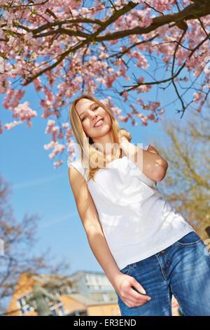 Blonde Mädchen stehen unter einem blühenden Kirschbaum Baum im Frühling - Stockfoto