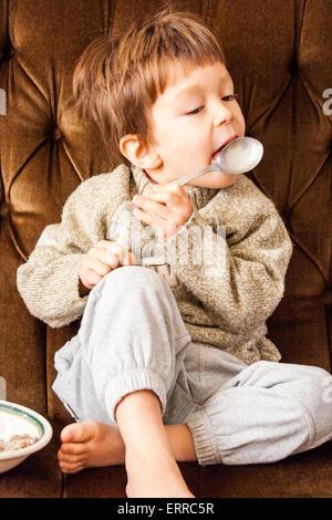 3 bis 5 Jahre alten kaukasischen Kind, junge auf Sofa lecken Löffel mit Wackelpudding von Getreide neben ihm gegenüber - Stockfoto