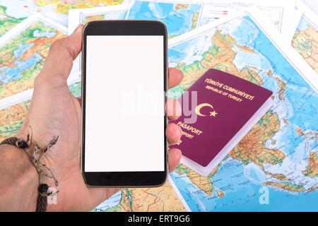 Detailansicht eines Smartphones mit leeren Bildschirm auf Seite halten und einen türkischen Pass auf einer Weltkarte - Stockfoto