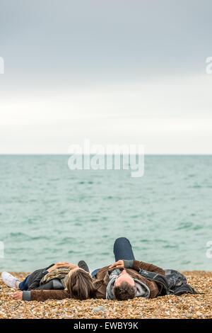 Ein paar entspannen Sie am Strand an der Küste in Brighton, East Sussex, England. - Stockfoto